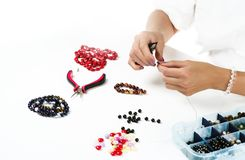 Jewelry making. Female hands with a tool. On a white background stock image