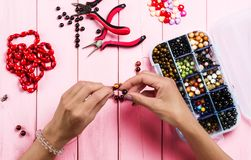 Jewelry making. Female hands with a tool on a pink. Background royalty free stock photography