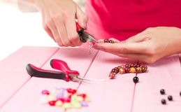 Jewelry making. Female hands with a tool on a pink table. Selective focus royalty free stock image
