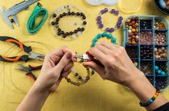 Jewelry making. Female hands with a tool on a yellow background.  royalty free stock image