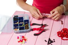 Jewelry making. Making bracelet of colorful beads. Female hands with a tool on a pink. Background royalty free stock images