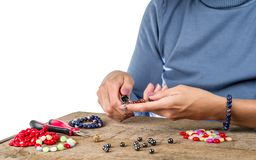 Jewelry making. Making bracelet from multi-colored beads on a rough wooden. Table royalty free stock image