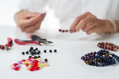 Jewelry making. Production bracelets and necklaces from multi-colored beads. Selective focus royalty free stock images