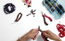 Jewelry making. Production bracelets and necklaces from multi-colored beads on a white. Background royalty free stock photography