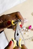 Jewelry making as a hobby #1. Jewelry making in progress, table with beads in the background royalty free stock photo