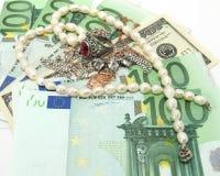 Jewelry on money background. Jewelry on money (euros and dollars) background Royalty Free Stock Photo