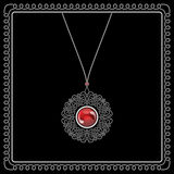 Jewelry pendant. Jewelry filigree pendant with red gem isolated on black in a swirl square frame Royalty Free Stock Image