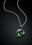 Jewelry pendant with green emerald on darck background Royalty Free Stock Image