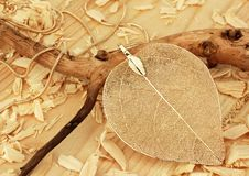 Jewelry pendant, shape of leaf, on wooden sawdust background royalty free stock photography