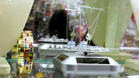 Beautiful girl in a jewelry store chooses jewelry. Jewelry, pendants, rings, earrings, bracelets, necklaces on the shop window twinkle rays from the falling stock video footage