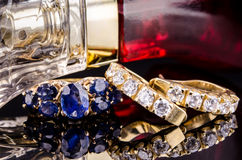 Jewelry and Perfume on black reflective surface. Stock Photo