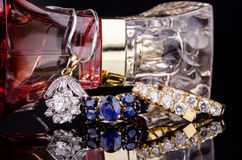 Jewelry and Perfume on black reflective surface. Royalty Free Stock Image