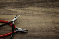 Jewelry pliers. Two jewelry pliers on a wooden background Royalty Free Stock Photo