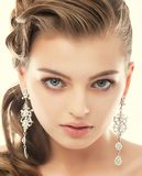 Jewelry. Portrait of Gorgeous Exquisite Woman with Shiny Earrings. Refinement Royalty Free Stock Photography