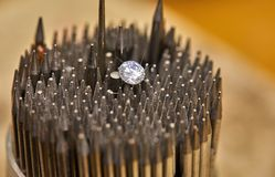 Jewelry production. The diamond is held with tweezers against the background stock image