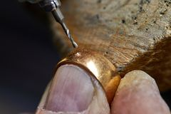 Jewelry production. The process of drilling holes in the ring stock photo