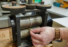 Jewelry production. Recycling raw materials. Jewelry craft on the metal-rolling machine stock photo
