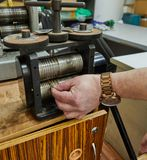 Jewelry production. Recycling raw materials. Jewelry craft on the metal-rolling machine stock image