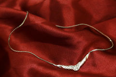 Jewelry on red silk. Beautiful jewelry on red silk royalty free stock photography