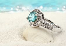 Jewelry ring with clean aquamarine gem on sand beach background. Jewelry ring with aquamarine gem on sand beach background stock image