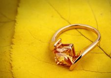 Jewelry ring with gemstone on yellow leaves background, copy spa royalty free stock photography