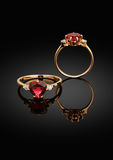 Jewelry ring with heart-shaped gem and diamonds on black backgro Stock Images