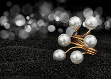Jewelry ring with pearls on black background with bokeh Royalty Free Stock Image