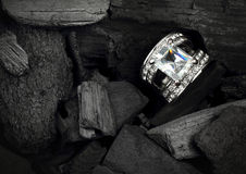 Jewelry ring witht big colourful diamond on black coal backgroun Royalty Free Stock Image