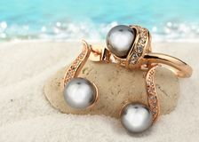 Jewelry set with black pearls on sand beach background, copy spa Stock Photography
