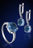 Jewelry set with brilliants on blue. Jewelry set with brilliants and gems on blue background Stock Image