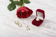 Jewelry set of golden ring in a gift box, earrings, necklace with pearls and red rose on white wooden background Stock Photos