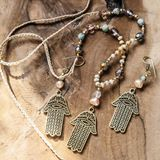 Jewelry set with Hamsa Fatima hand symbol. And stone beads on wooden background stock photography