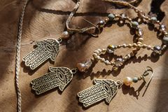 Jewelry set with Hamsa Fatima hand symbol. And stone beads on wooden background stock photo