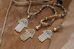 Jewelry set with Hamsa Fatima hand symbol. And stone beads on wooden background royalty free stock photos