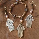 Jewelry set with Hamsa Fatima hand symbol. And stone beads on wooden background royalty free stock image