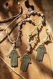 Jewelry set with Hamsa Fatima hand symbol. And stone beads on wooden background stock photos