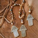 Jewelry set with Hamsa Fatima hand symbol. And stone beads on wooden background royalty free stock photo