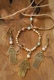 Jewelry set with Hamsa Fatima hand symbol. And stone beads on wooden background stock image