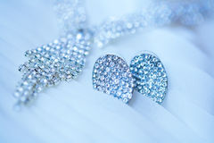 Jewelry set on a wedding drees background. Jewelry set on a wedding drees Royalty Free Stock Image