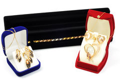 Jewelry sets. Shopping for gold jewelry, sets inside boxes, on white Royalty Free Stock Photography