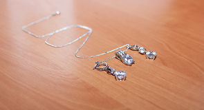 Jewelry and silver chain, on wooden desk. Stock Photo