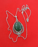 Jewelry from silver with a nephrite. On a red background Stock Image