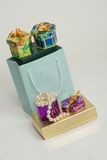 Jewelry sized bag and gift box. A light blue small gift bag with small jewelry sized boxes on top.In the front is a gold box and a smaller box with a string of Stock Photos