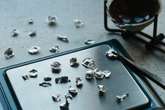 Jewelry tools. Jewellery. Goldsmith workplace, workspace on light background. Hand craft. Workshop. Manufacturing. Weigh. Scales with granules of metal silver Royalty Free Stock Images