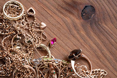 Jewelry On Wood. Pile of gold jewelry on wooden surface with copy space Stock Photo