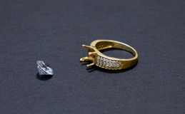 Jewelry work, gold ring with a diamond, preparation for installing a stone on a ring, dark background. Close-up stock image