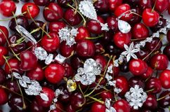 Jewels at cherries. Jewels at fruit red ripe cherries berry background Royalty Free Stock Images
