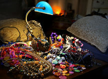 Jewels and necklaces on the jewelry pile below the lamp Stock Photos
