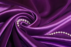 Jewels on purple satin. Pearl necklace on purple satin Royalty Free Stock Photo