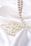 Jewels on white satin Royalty Free Stock Photos